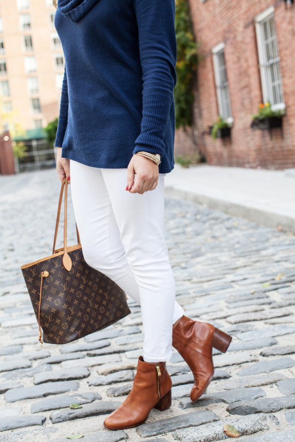 white jeans tan boots navy sweater louis vuitton