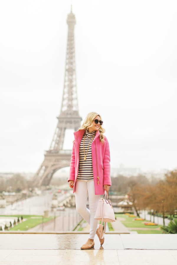 pink coat in front of the eiffel tower