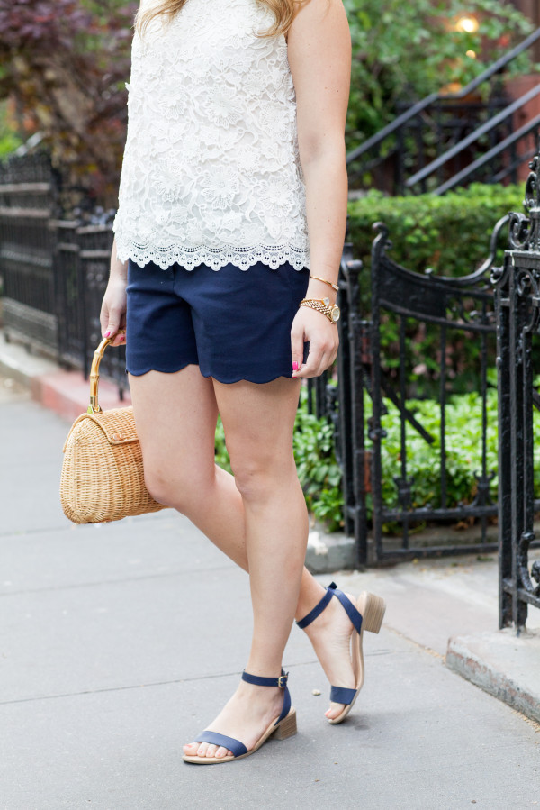 white lace top, navy blue scalloped shorts, wicker bag, navy leather sandals