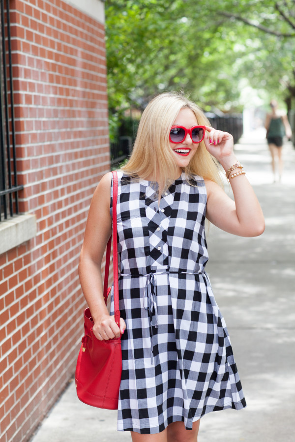 black and white gingham dress with red bucket bag