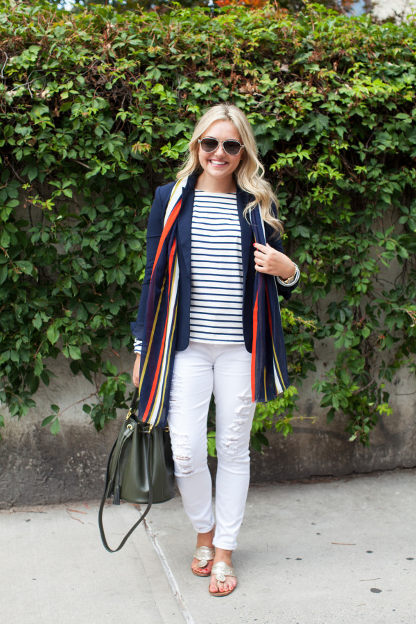Bows & Sequins wearing a striped shirt, blue blazer, and white jeans.