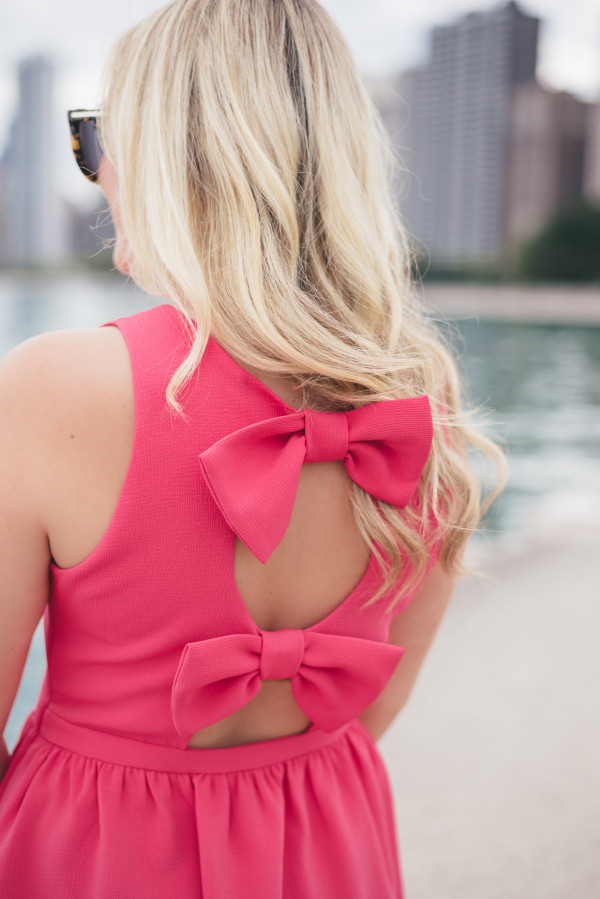 Bows & Sequins styling a pink bow back dress.