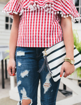 red gingham top with ruffle and pom poms, navy striped monogram clutch with tassel, ripped jeans