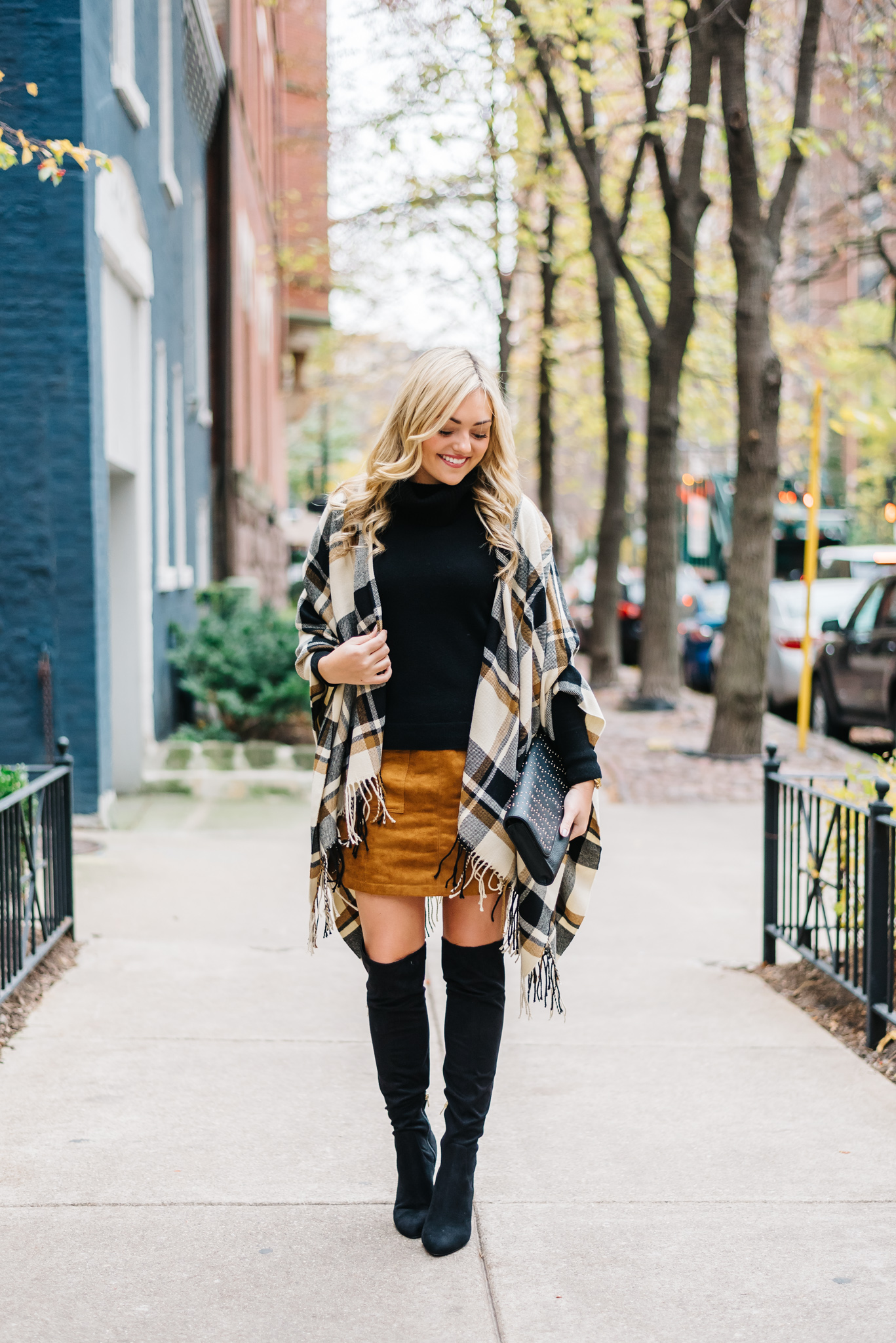 Jessica Sturdy styling a plaid cape over a suede skirt and over the knee boots for a cute fall outfit in Chicago.