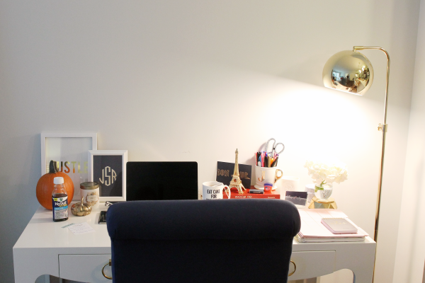 white desk, navy chair, gold floor lamp