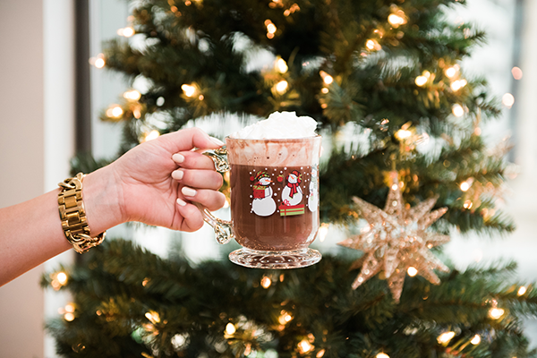 Mug of Hot Cocoa with Whipped Cream in front of a Christmas Tree