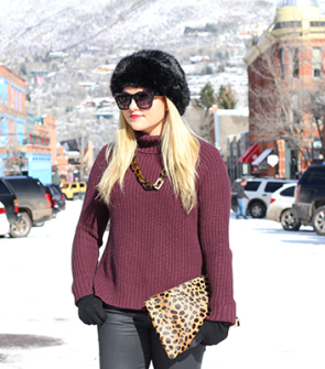 Fashion blogger wearing a faux fur hat, Valentino rockstud sunglasses, chunky turtleneck sweater, and Clare V Leopard Clutch in Aspen.