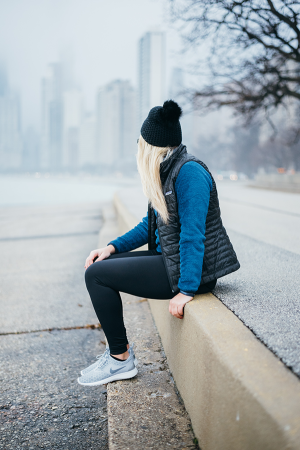 Blonde wearing Patagonia vest and fleece pullover with a black pom pom beanie, tights, and grey Nike sneakers in front of a foggy Chicago skyline.