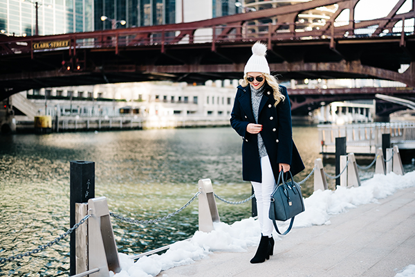 navy blue military inspired coat with white jeans and black booties