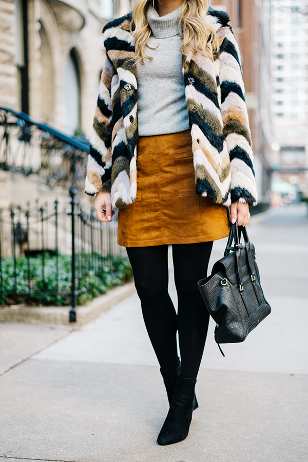 Bows & Sequins styling a faux fur jacket for winter: grey turtleneck, suede skirt, black tights, booties