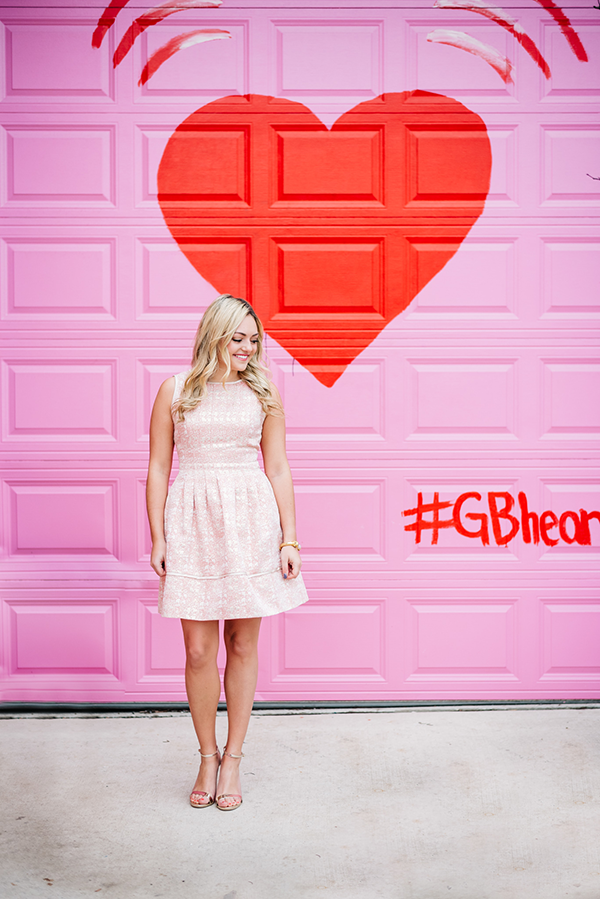 Bows & Sequins styling a light pink dress in front of a pink and red heart wall in Chicago.