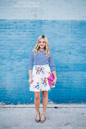 Bows & Sequins wearing a blue and white striped shirt with a floral skirt, pink clutch, and glitter pumps.