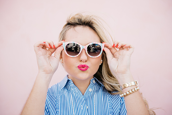 Bows & Sequins wearing striped sunglasses and bright pink lipstick.