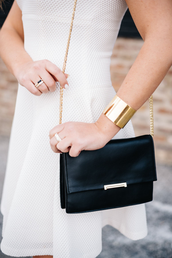 black leather gold chain clutch crossbody bag, white dress, gold cuff