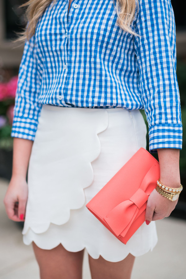 blue gingham shirt, white scalloped skirt, coral bow clutch