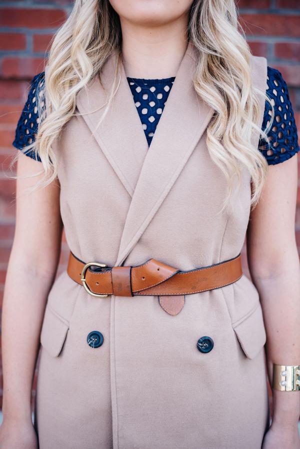 navy eyelet dress, camel vest, leather belt