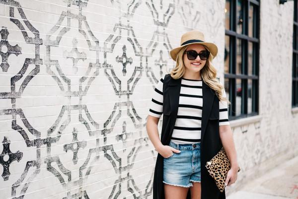 panama hat striped tee shirt long black vest denim jean shorts leopard clutch