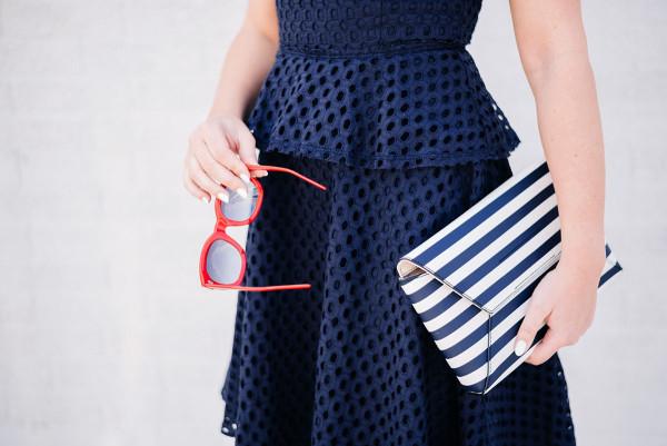 red sunglasses, navy eyelet peplum dress, striped clutch