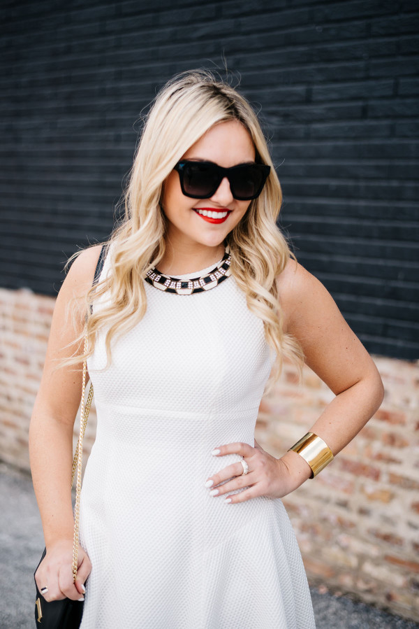 white dress with black and gold accessories