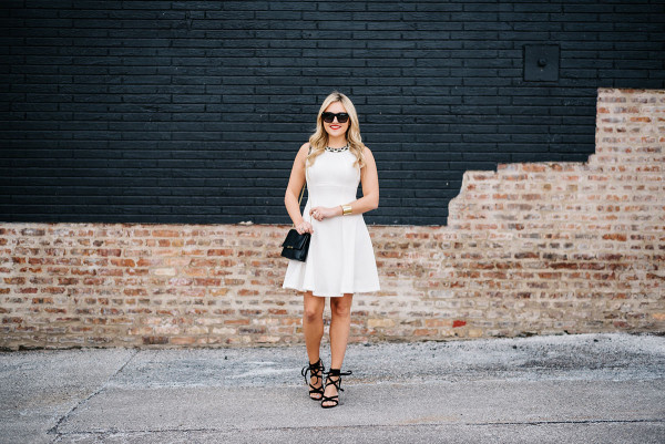 white fit and flare dress with black handbag and black sandals