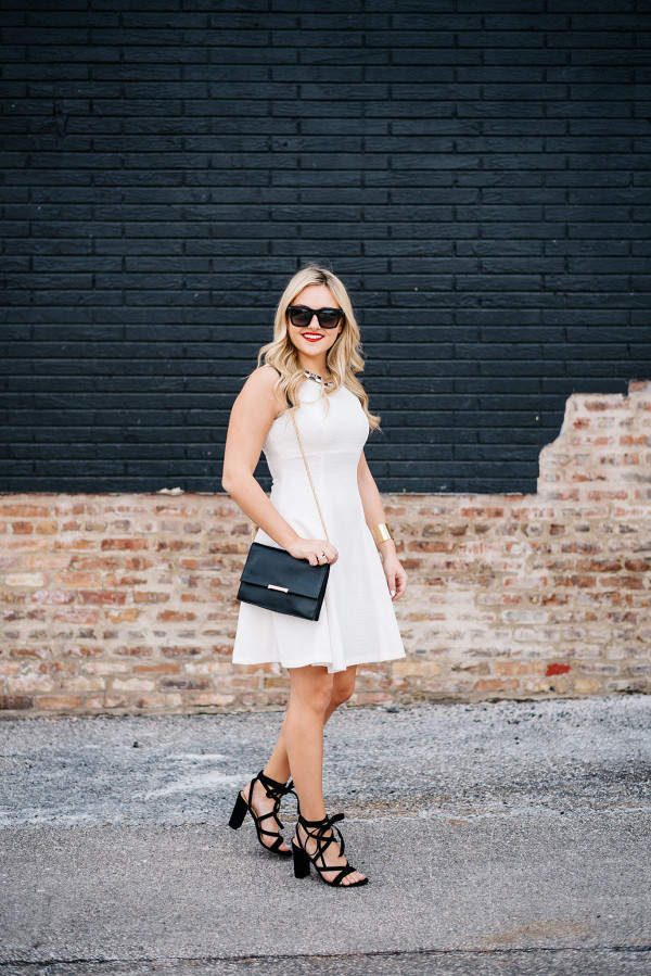 white fit and flare dress with black shoes and accessories