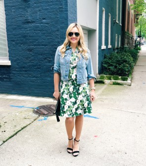 Bows & Sequins wearing an a-line leaf print dress, a denim jacket, and black ankle-strap heels.