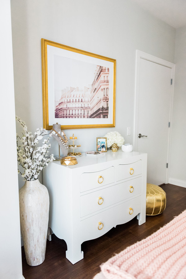 Blogger Jessica Sturdy of Bows & Sequins shares her Chicago Parisian-chic bedroom design. Bungalow 5 White Lacquer Jacqui Dresser with brass drawer pulls, Parisian facade print in an antique gold frame from Simply Framed, gold Moroccan leather pouf.
