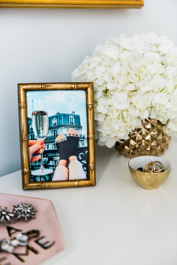 Blogger Jessica Sturdy of Bows & Sequins shares her Chicago Parisian-chic bedroom design. Gold bamboo frame, white hydrangeas, gold CB2 colada vase.