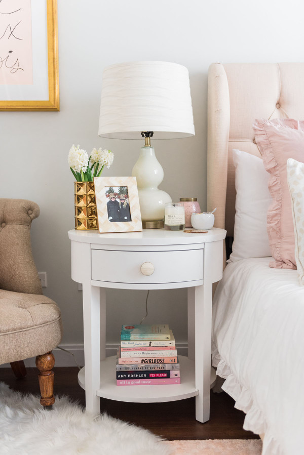 Blogger Jessica Sturdy of Bows & Sequins shares her Chicago Parisian-chic bedroom design. White round nightstands with glass gourd lamps and bone inlay knobs and picture frame.