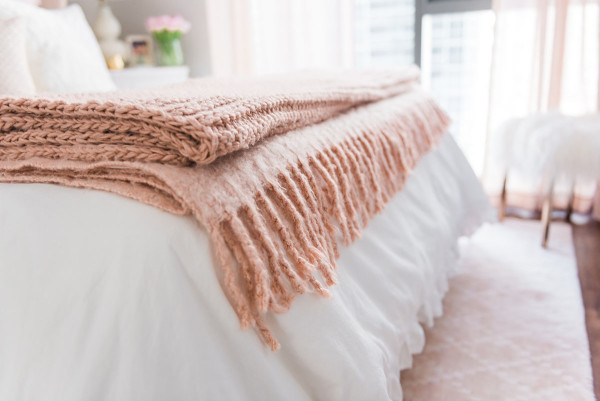 Blogger Jessica Sturdy of @bowsandsequins shares her Chicago Parisian-chic bedroom design. Blush pink West Elm throw blankets, white Crane & Canopy ruffled duvet cover, Pier 1 blush pink rug.