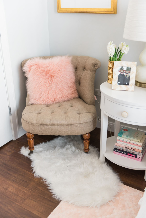 Blogger Jessica Sturdy of Bows & Sequins shares her Chicago Parisian-chic bedroom design. Tufted linen chair, fuzzy pink pillow, white shag animal rug.