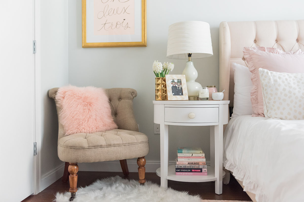 Blogger Jessica Sturdy of Bows & Sequins shares her Chicago Parisian-chic bedroom design. Un Deux Trois blush pink print, tufted linen chair, white faux shag animal skin rug, white round nightstand, white glass gourd lamps.