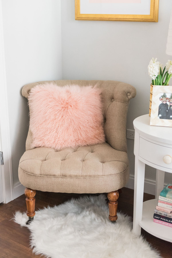 Blogger Jessica Sturdy of Bows & Sequins shares her Chicago Parisian-chic bedroom design. Tufted linen chair, white faux shag animal skin rug, white round nightstand, white glass gourd lamps.