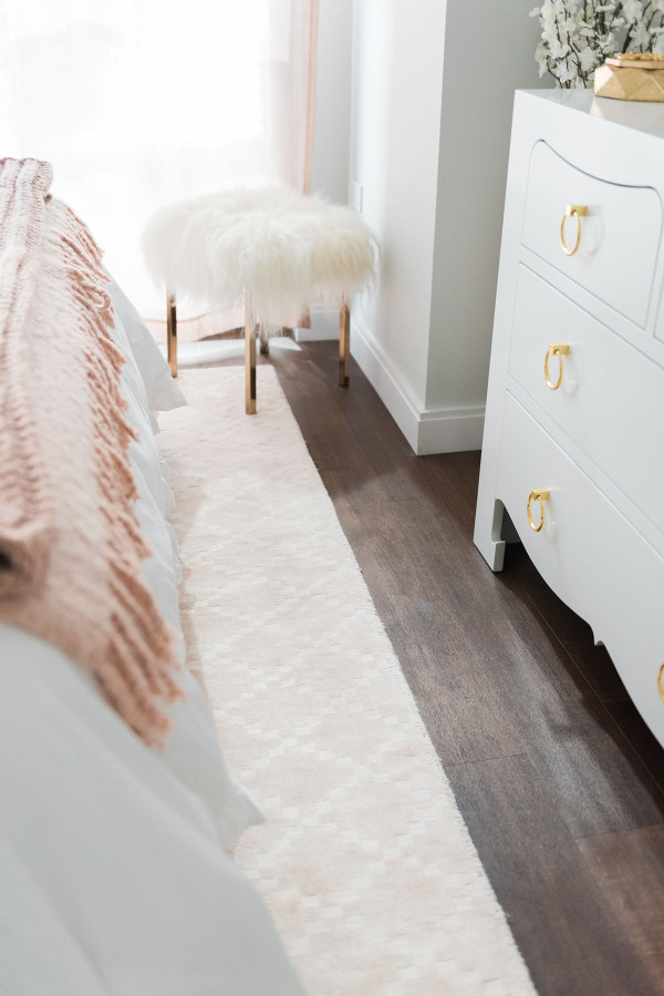 Blogger Jessica Sturdy of @bowsandsequins shares her Chicago Parisian-chic bedroom design. // Blush Pink Rug, White Bedding, White Bungalow 5 Jacqui Lacquer Dresser with Brass Pulls, Gold Moroccan Leather Pouf, CB2 Shag Stool with gold legs