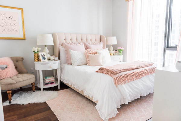 Blogger Jessica Sturdy of Bows & Sequins shares her Chicago Parisian-chic bedroom design. Tufted linen headboard, blush pink rug, and white, ruffled bedding.