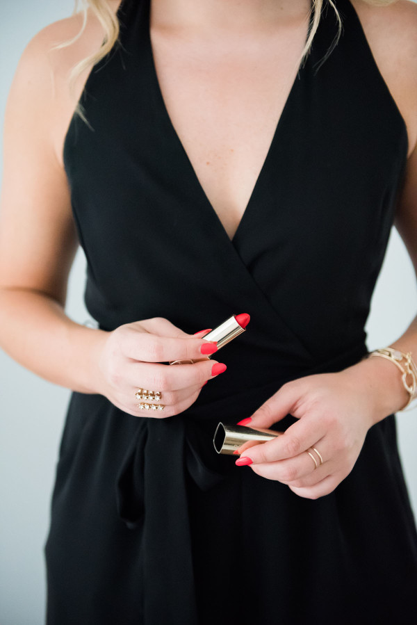 red lipstick in a gold tube, black halter romper, gold rings, getting ready