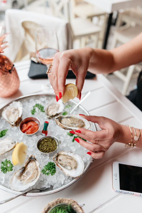 squeezing lemon on oysters rosé summer
