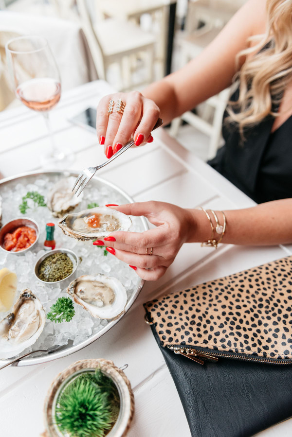 girl eating oysters, glass of rosé, leopard clutch