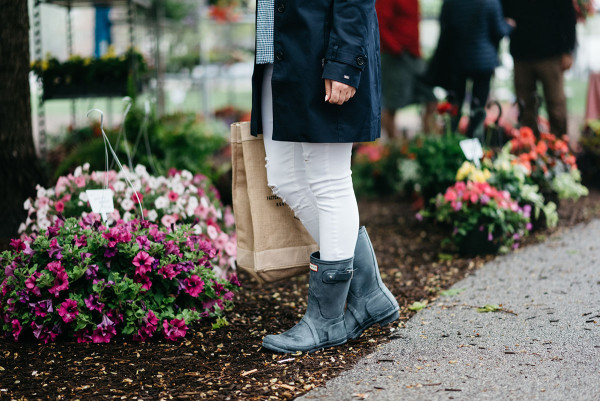 Bows & Sequins at Green City Market in Lincoln Park wearing a navy Tommy Hilfiger trench coat, a gingham top, white jeans, an Apolis farmers market straw tote, and blue Hunter rain boots.