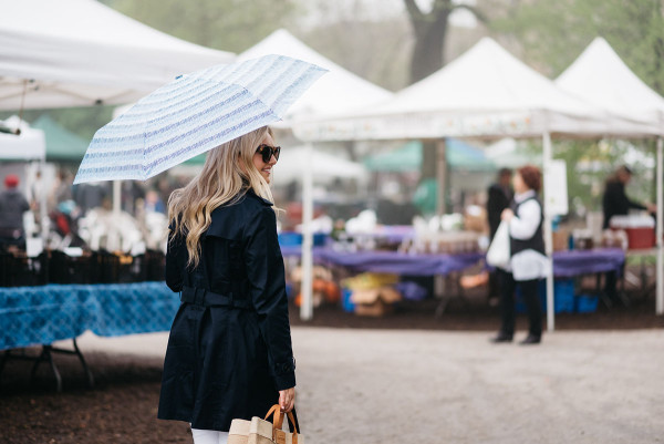 Bows & Sequins at Green City Market in Lincoln Park wearing a navy Tommy Hilfiger trench coat and a blue printed umbrella.