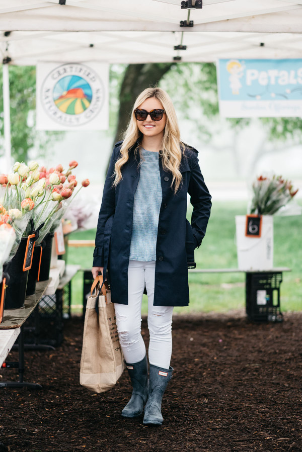 Bows & Sequins at Green City Market in Lincoln Park wearing a navy Tommy Hilfiger trench coat, a gingham top, white jeans, and blue Hunter rain boots.