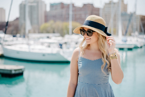Bows & Sequins at Belmont Harbor in Chicago wearing a blue Old Navy gingham dress, a sun hat from Tuckernuck, a J.McLaughlin wicker tote, and a Kate Spade striped silk scarf.