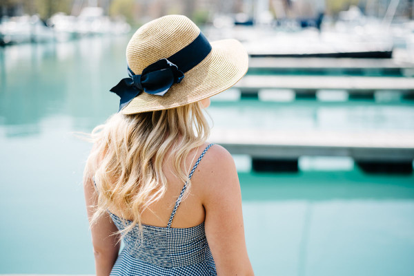 Bows & Sequins at Belmont Harbor in Chicago wearing a blue and white gingham dress from Old Navy and a sun hat from Tuckernuck with a navy blue grosgrain bow.