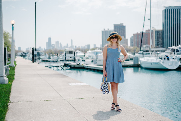 Bows & Sequins at Belmont Harbor in Chicago wearing a blue Old Navy gingham dress, a sun hat from Tuckernuck, Ralph Lauren navy wedges, a J.McLaughlin wicker tote, and a Kate Spade striped silk scarf.