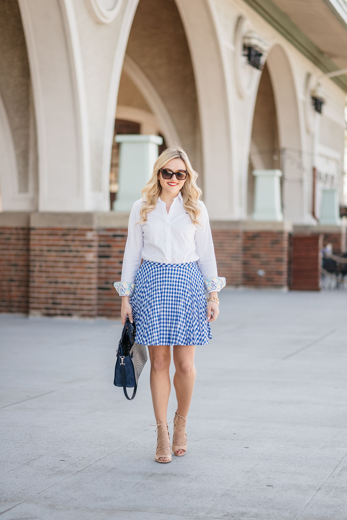 Bows & Sequins wearing a work outfit: White Oxford Shirt, Blue Gingham Skirt, Nude Lace-Up Heels, and a Navy Blue Kate Spade Bag.