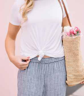 Bows & Sequins wearing a knotted white t-shirt, blue and white striped wide-leg linen pants, and a straw market tote filled with pink tulips.