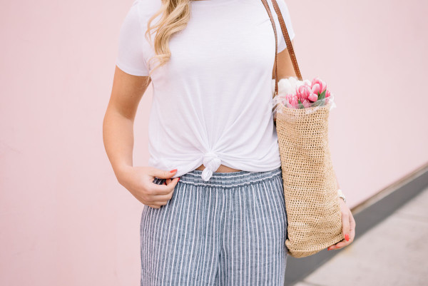 knotted tee shirt, blue and white linen pants, straw market tote, pink tulips