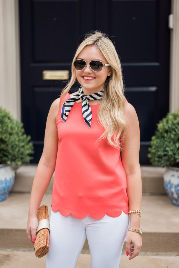 Bows & Sequins wearing a navy blue and white striped silk neck scarf with a coral scalloped hem tank top, white jeans, and a wicker clutch.