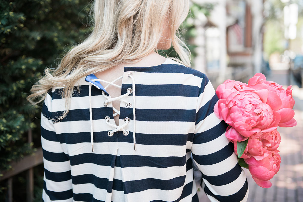 Bows & Sequins wearing a Tommy Hilfiger striped shirt with a bouquet of pink peonies in Old Town Chicago.
