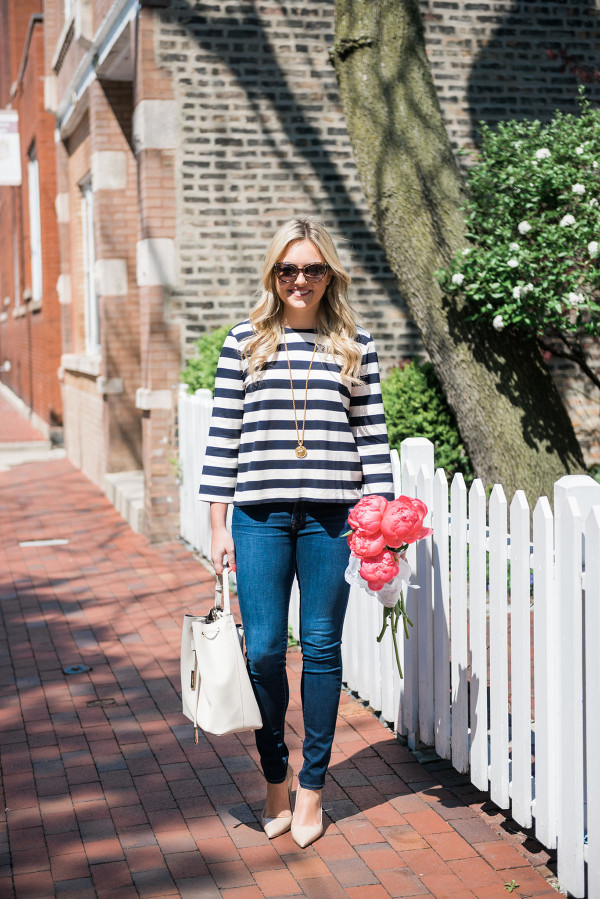 Bows & Sequins wearing a Tommy Hilfiger striped shirt, J Brand jeans, Kate Spade pumps, and a white bucket bag with a bouquet of pink peonies in Old Town Chicago.